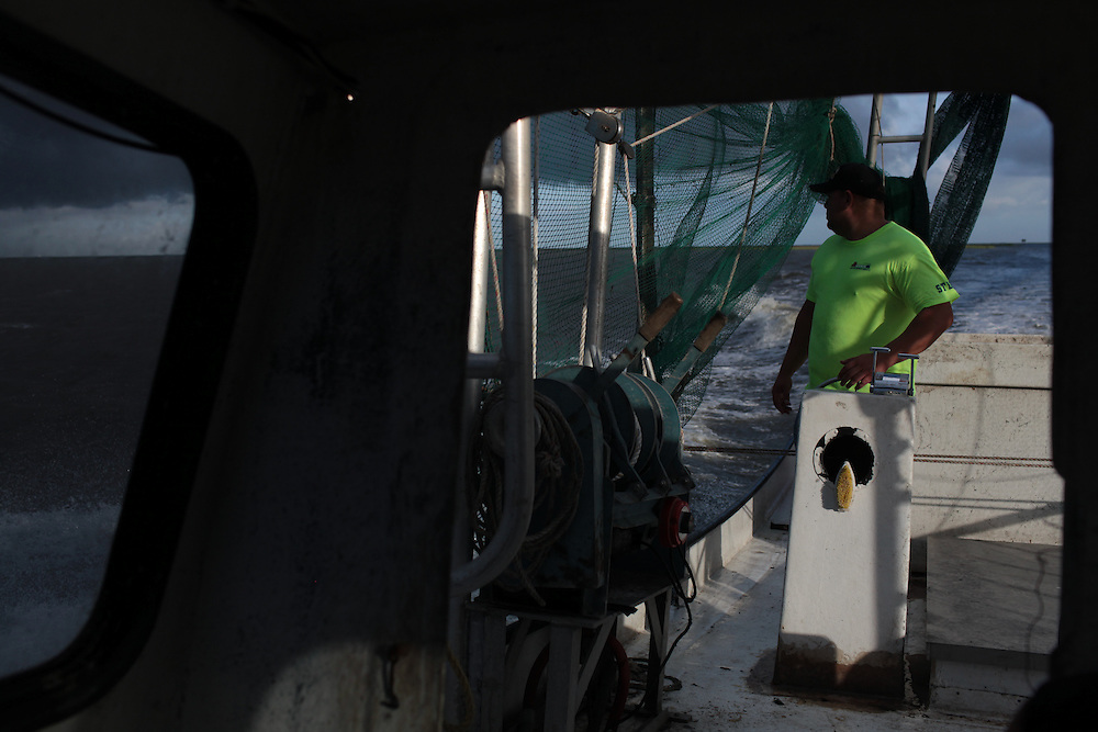 Eric Melerine watching a storm come in while pulling in hard boom around Pelican Island, LA August 30, 2010.
