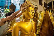 """03 DECEMBER 2012 - BANGKOK, THAILAND: Workers pull a statue of the Buddha into their workshop at closing time on Bamrung Muang Street in Bangkok. Thanon Bamrung Muang (Thanon is Thai for Road or Street) is Bangkok's """"Street of Many Buddhas."""" Like many ancient cities, Bangkok was once a city of artisan's neighborhoods and Bamrung Muang Road, near Bangkok's present day city hall, was once the street where all the country's Buddha statues were made. Now they made in factories on the edge of Bangkok, but Bamrung Muang Road is still where the statues are sold. Once an elephant trail, it was one of the first streets paved in Bangkok. It is the largest center of Buddhist supplies in Thailand. Not just statues but also monk's robes, candles, alms bowls, and pre-configured alms baskets are for sale along both sides of the street.      PHOTO BY JACK KURTZ"""