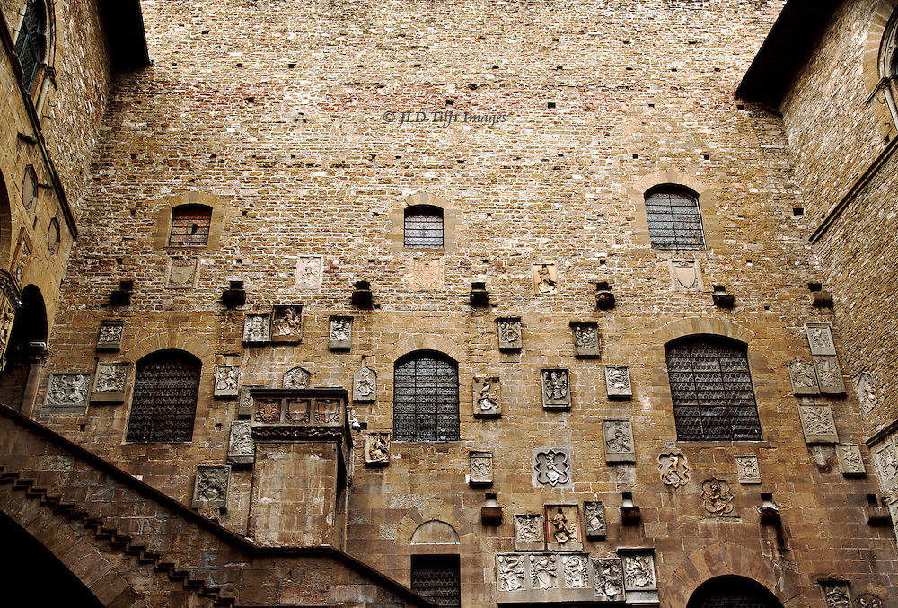 Courtyard wall of the Bargello studded with carved stone coats of arms of various Florentine families.