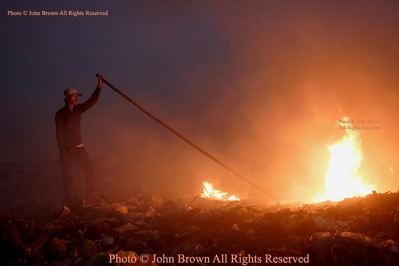 "A worker attends to a pile of burning garbage at The Stung Meanchey Landfill in Cambodia. Fires spew noxious methane gas into the air and approximately 2000 people who scavenge here must endure these conditions daily to earn their livings. The dump is nicknamed ""Smokey Mountain""."