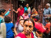 01 AUGUST 2015 - KATHMANDU, NEPAL: Buddhist women leave a service at Shree Gha Stupa, a Buddhist stupa near Durbar Square in Kathmandu.       PHOTO BY JACK KURTZ