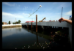 May 29th, 2006. New Orleans, Louisiana. Memorial Day. Former residents of Lakeview and other New Orleans residents throw flowers from a bridge over the 17th Street canal close to where the levee breached during Hurricane Katrina, destroying the once affluent neighbourhood.