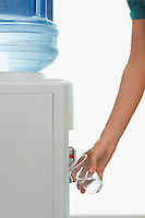 Man pouring drink from water cooler indoors close-up of arm and hand
