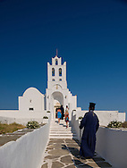 A priest arriving for a wedding at the Chrysopighi Monastery on Sifnos, The Cyclades, Greek Islands, Greece, Europe