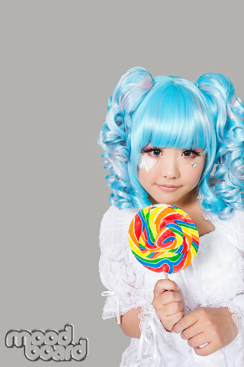 Portrait of cute young woman dressed as a doll holding lollipop over gray background