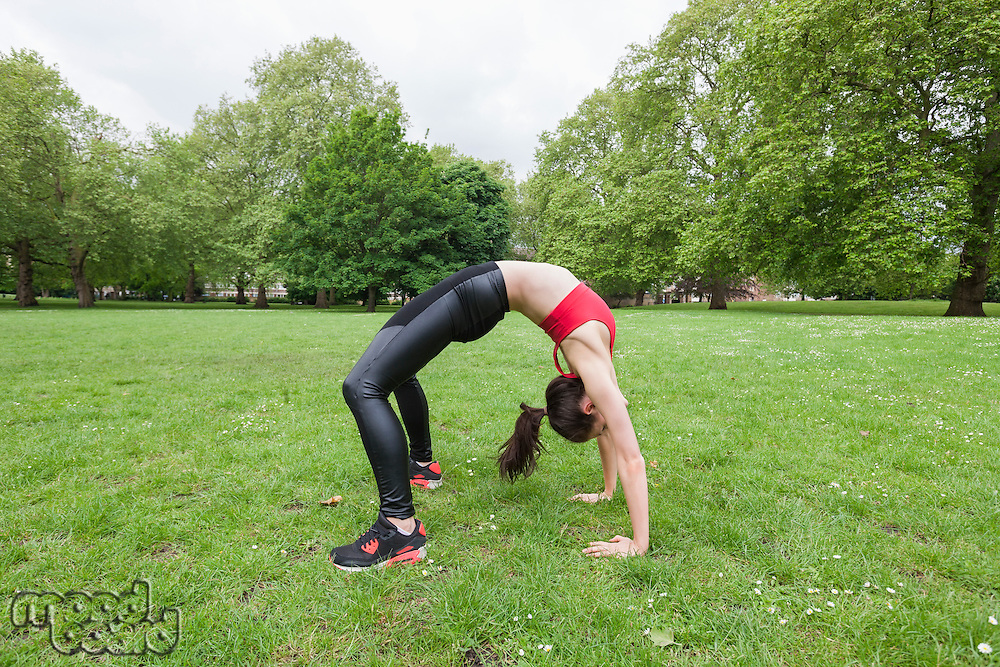 Full length side view of fit woman exercising in park