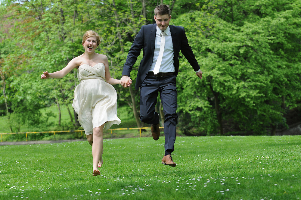 Braut und Bräutigam hüpfen über eine Wiese |     young couple on wedding day jumping over a meadow |