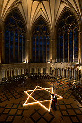 © Licensed to London News Pictures. 24/01/2019. York UK. The Revd Canon Dr Chris Collingwood, York Minster's Canon Chancellor lights one of the 600 candle's that make up the shape of the star of David in York Minster this evening to mark International Holocaust Memorial Day in memory of 6 million Jewish people murdered by the Nazis during the second world war. Photo credit: Andrew McCaren/LNP