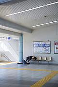 En pojke har somnat på en tågstationen, Japan