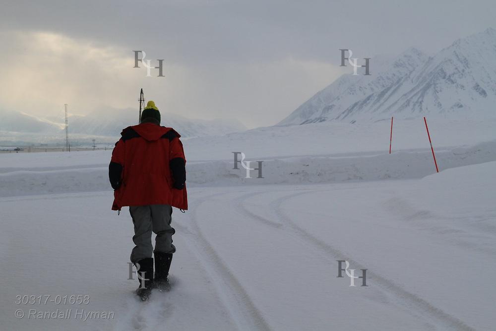 Man walks along snowy road outside the international science village of Ny-Alesund on Spitsbergen island in Kongsfjorden; Svalbard, Norway.