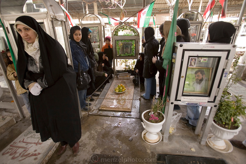 In the Martyr's section of the Behesht Zahra cemetery in Tehran, Iran, a family memorializes a family member killed during the Iran-Iraq war 1980-1988. Other parts of the cemetery are devoted to the rest of the population. Memorializing family members who have died is an important part of Islamic and Persian culture in Iran and follows a prescribed series of graveside visits. Iranians meet at the graves, bringing food to share with each other and passersby who pay their respects.