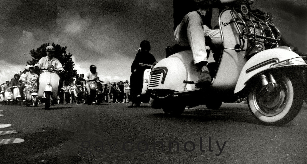 Sunday morning run out at the Isle of white scooter rally in 2000 .Total gridlock ensued not long after takeoff .Taken on a Canon T90 ,HP5 pushed to 1600 on a very sunny day .Only ran 10 photos at 1600 and then resorted to 400 ,easy to cut off in the darkroom and develop seperately .I had the pleasure of being driven round the island on a 3 wheeler Vespa/Robin ,Lock Stock by Doyley ,Stockport Crusaders .