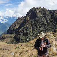 Peru, Hiking party's guide playing flute at summit of Abra de Runkuracay pass along Inca Trail to Machu Picchu