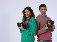 Portrait of young woman and young man holding cameras studio shot
