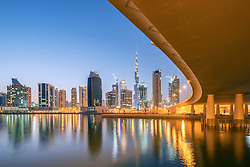 Skyline of towers at dusk in Business Bay next to bridge across the Creek in Dubai United Arab Emirates