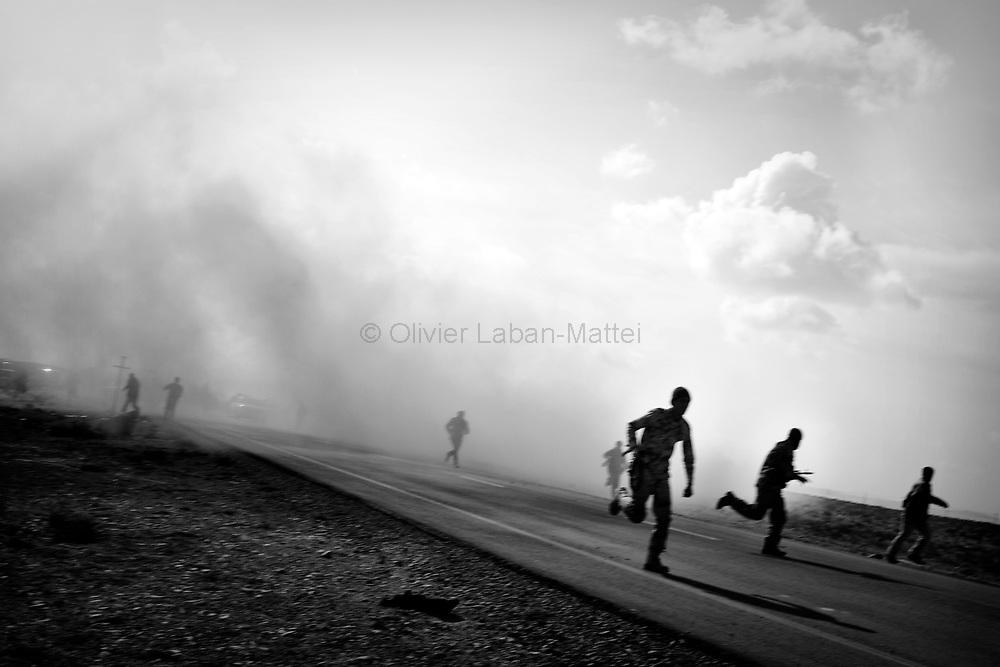 Des combattants rebelles fuient des bombardements de l'armée loyaliste, le 1er avril 2011 sur la ligne de front à quelques kilomètres de la ville de Brega.