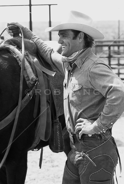cowboy standing by a horse outdoors