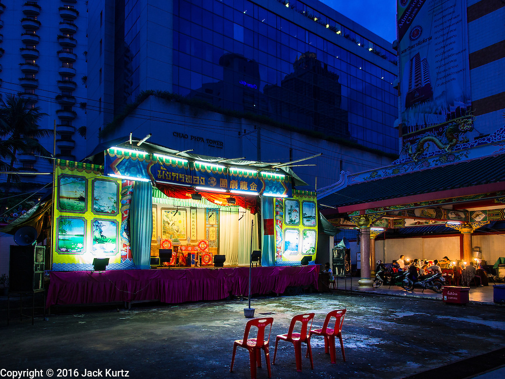 """30 JUNE 2016 - BANGKOK, THAILAND: Performers put on the makeup (left) while the stage sits empty before a Chinese opera performance at Chiao Eng Piao Shrine in Bangkok. Chinese opera was once very popular in Thailand, where it is called """"Ngiew."""" It is usually performed in the Teochew language. Millions of Chinese emigrated to Thailand (then Siam) in the 18th and 19th centuries and brought their culture with them. Recently the popularity of ngiew has faded as people turn to performances of opera on DVD or movies. There are about 30 Chinese opera troupes left in Bangkok and its environs. They are especially busy during Chinese New Year and Chinese holidays when they travel from Chinese temple to Chinese temple performing on stages they put up in streets near the temple, sometimes sleeping on hammocks they sling under their stage.       PHOTO BY JACK KURTZ"""