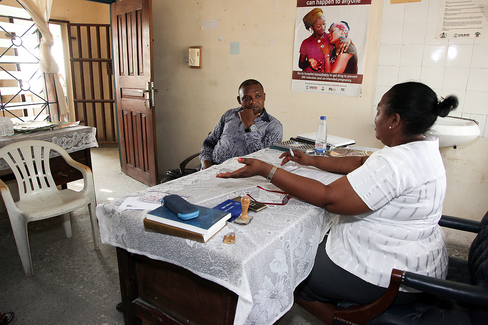 INDIVIDUAL(S) PHOTOGRAPHED: Ibiam Azu Agwu (left) and N/A (right). LOCATION: Family Health Clinic, Moor Road, Calabar, Cross River, Nigeria. CAPTION: Ibiam Azu Agwu, who manages the HFG Project in Cross River, speaks with a staff member at the Family Health Clinic.