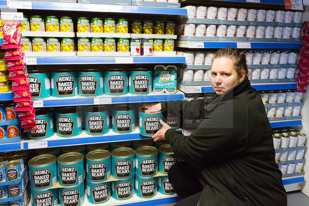"© Licensed to London News Pictures. 19/12/2014. London, UK. A member of staff with giant tins of baked beans costing £2 in the Community Shop. The Community Shop opened this week in Gipsy Hill, South London and is a ""social supermarket"", which sells heavily-discounted surplus food that would otherwise be thrown away. Food is received from retail brands such as Marks & Spencer, Asda, Tesco, Innocent and Muller and many more. The shop works on a membership basis only, serving residents who are on income support and aimed at people who are in work, but low waged and for those working hard to find a job. Photo credit : Vickie Flores/LNP"