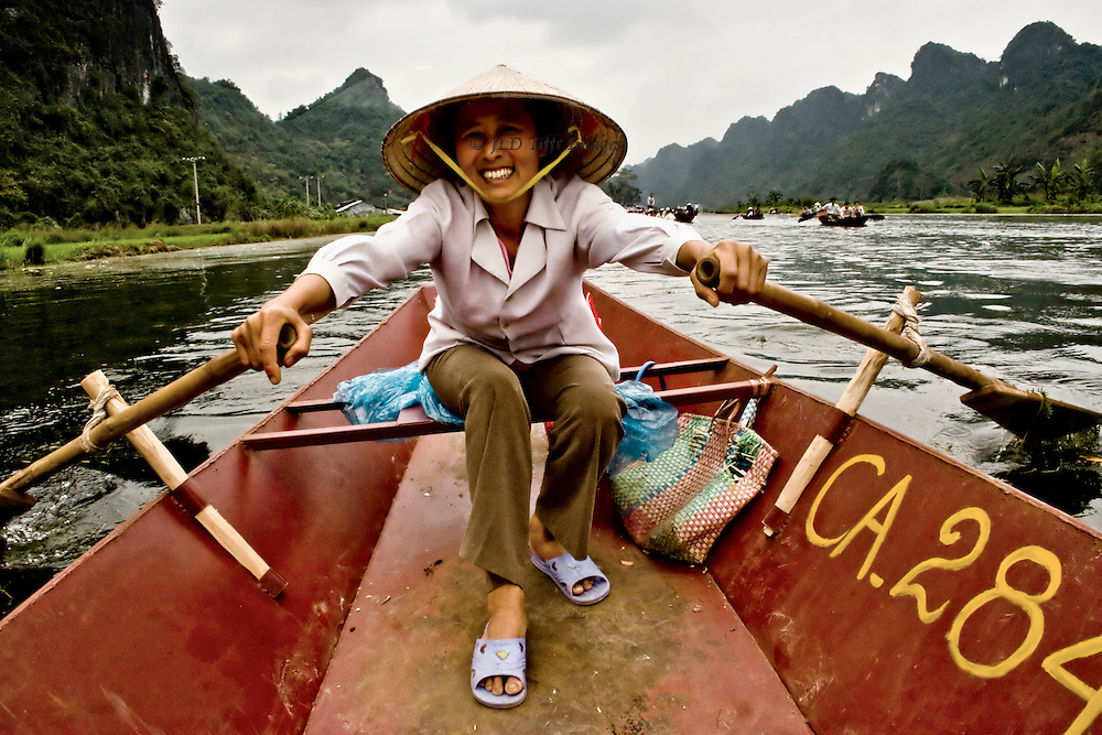 Vietnamese woman oarsman in her rowboat, smiling, as she rows passengers to the Perfume Pagoda (Chua Huong) up the Yen River from My Duc hamlet. She supports herself and a son with this employment.  River, mountains, and other rowboats filled with passengers, visible beyond.  The rowboat is red-painted metal, worn, battered, but maintained.