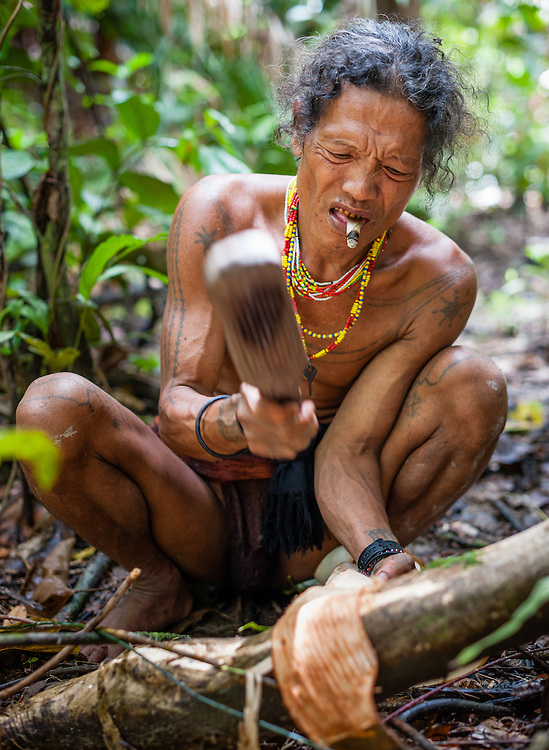 Mentawai indigenous man making a loincloth (Indonesia).