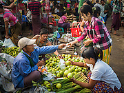 """25 OCTOBER 2015 - INSEIN, MYANMAR:  Shoppers buy guava in Danyin Market (also known as Da Nyin) in Insein, Myanmar, about 90 minutes from Yangon. Vendors in the market sell just about everything people in the area need, but mostly it's a """"wet market"""" with fruits, vegetables and meats. Most people in Myanmar still do not have refrigerators in their homes, so people go to market almost every day.    PHOTO BY JACK KURTZ"""