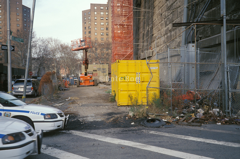 Two NYPD cars parked at a construction site