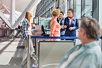 Mature woman on board giving her passport and boarding pass in airport