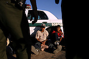 Illegal aliens sit against a patrol car after being apprehended by the U.S. Border Patrol in the desert near El Centro, Calif. on Wednesday, March 29, 2005. The five aliens walked for about three hours through the desert, making it five miles into the U.S. before being nabbed by the Border Patrol.<br />