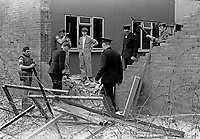 Police and military personnel inspect the damage caused by a Provisional IRA bomb planted 25th April 1971 at Springfield Road Police Station, Belfast, N Ireland. Both police and army operate from the station. 197105250217<br />