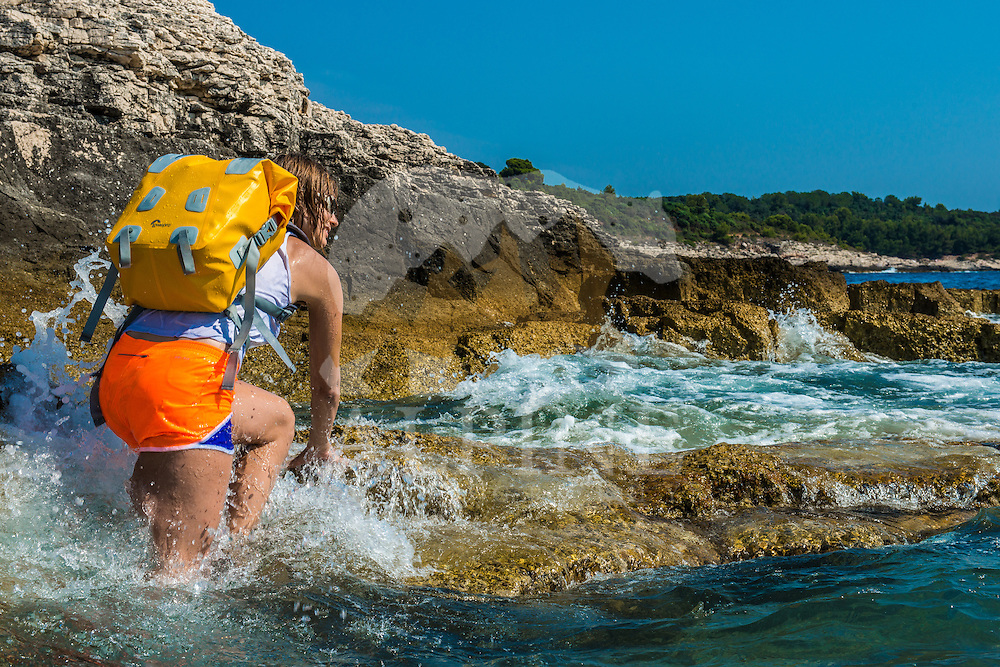 A female photographer wearing a yellow waterproof backpack as seen on a sunny Summer day walking on the coast line of Croatian natural park of Premantura.