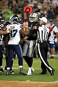 NFL referee Clay Martin (19) breaks up a scuffle between Seattle Seahawks defensive end David Bass (47) and Oakland Raiders rookie tight end Pharaoh Brown (81) during the 2017 NFL week 4 preseason football game against the Oakland Raiders, Thursday, Aug. 31, 2017 in Oakland, Calif. The Seahawks won the game 17-13. (©Paul Anthony Spinelli)