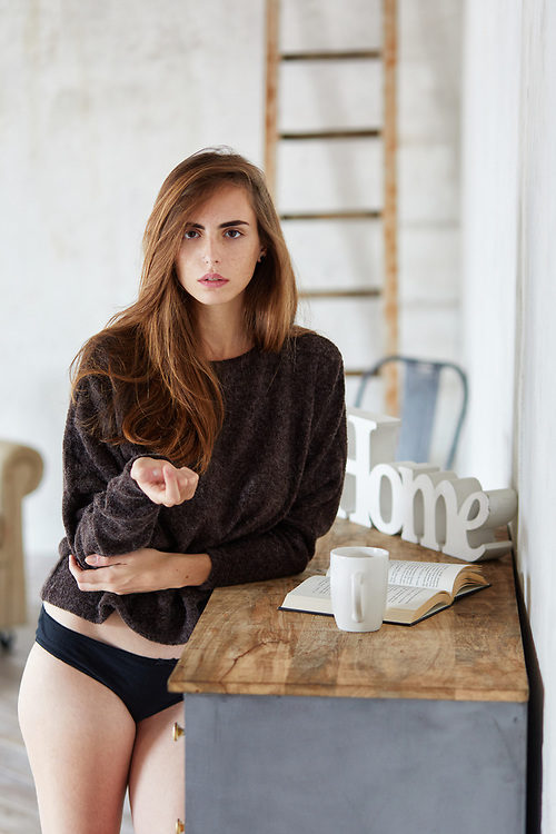 Authentic and attractive young woman looks towards the camera while standing a the room by a wooden table