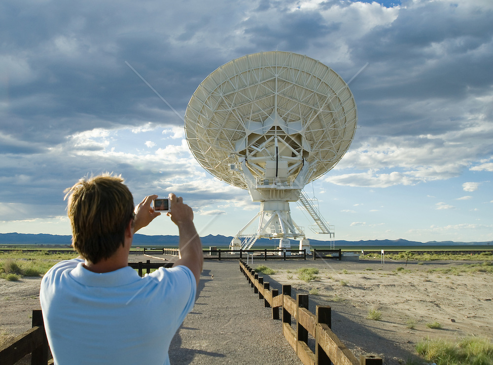 Back of a man taking a digital picture of a Very Large Array satellite dish