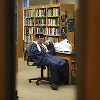 Baldwyn High School senior Noah Hancock looks at his phone as he waits with his classmates in the library before the start of Friday night's graduation ceremony at the school.