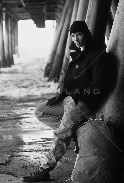 Man standing beside duffle bag underneath a pier