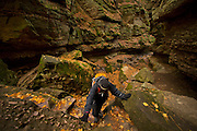 A woman hikes in the gorge of Parfrey's Glen, Wisconsin's first State Natural Area near Baraboo, Wisconsin. The walls of the glen are sandstone with embedded pebbles and boulders of quartzite.