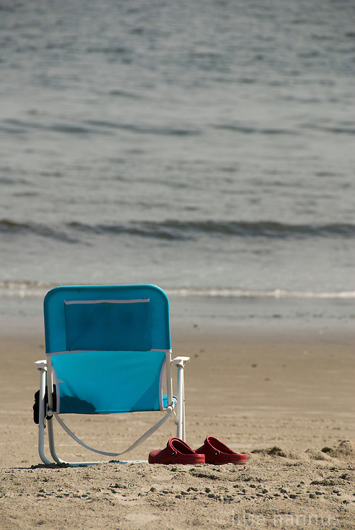 Red Crocs and a blue beach chair await the return of their owner at the beach at Coney Island, Brooklyn, New York.