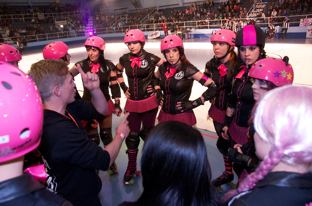 The Raging Warmones Coach Nic talks to skaters during half time at The C-Max Roller Derby league Deathrow Demolition Derby, July 28 2012. The Raging Whoremones versus the Thundering Hellcats, Johannesburg, South Africa.