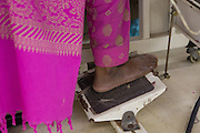 A garment worker powers the foot pedal of a sewing machine inside  Epyllion Group garment factory in Bangladesh.