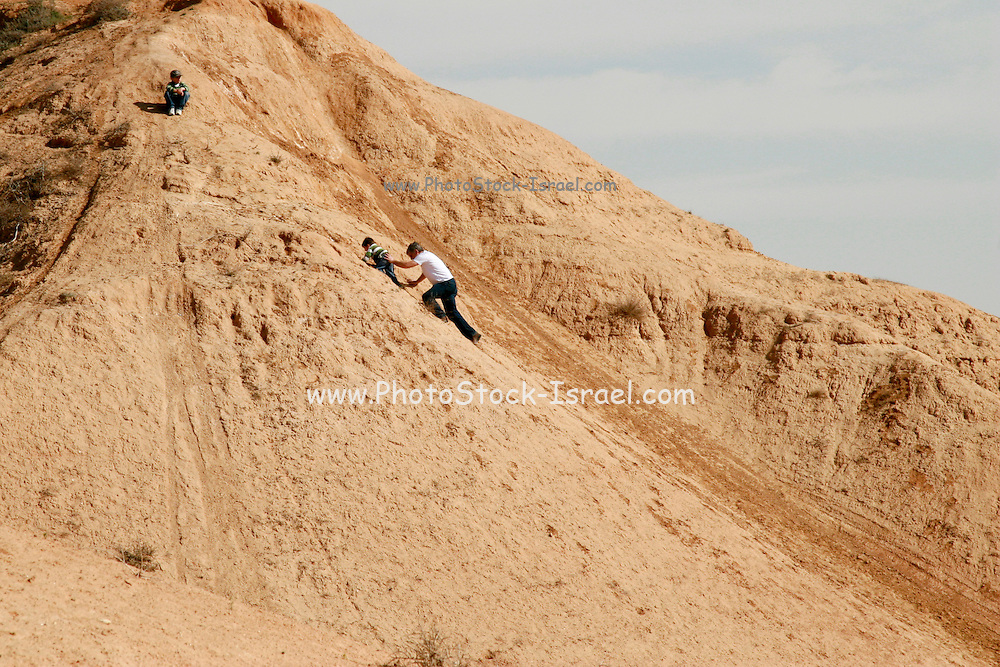 Israel, Negev plains, Nitzana father helps child crawl up a sand dune