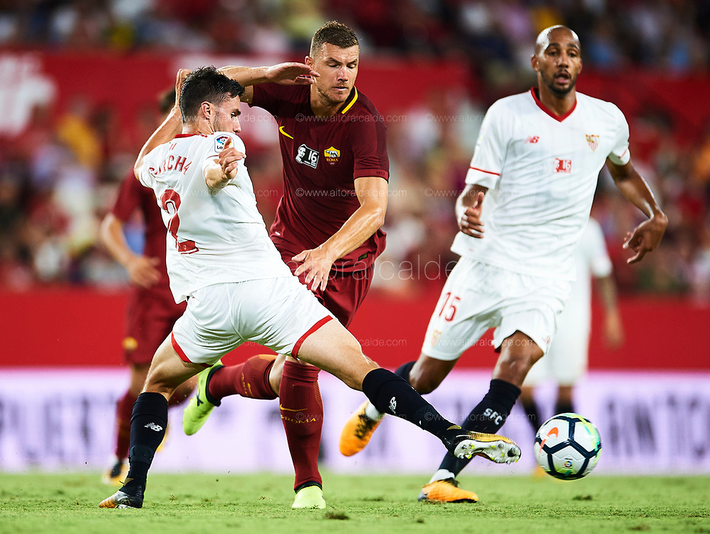 SEVILLE, SPAIN - AUGUST 10:  Edin Dzeko of AS Roma (C) competes for the ball with Sebastien Corchia of Sevilla FC (L) during a Pre Season Friendly match between Sevilla FC and AS Roma at Estadio Ramon Sanchez Pizjuan on August 10, 2017 in Seville, Spain. (Photo by Aitor Alcalde/Getty Images)
