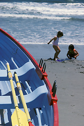 Two children play in beach sand at the shore.  Lifeguards boat and oars in foreground.