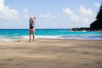 Female hiker standing and looking out toward the surf on  Hanakapiai Beach while taking a digital photograph  The Na Pali Coast of Kauai, Hawaii.