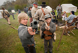 © London News Pictures. 08/04/2012. South Okendon, UK.  Cousins Bailey Haskett aged 10 (left) and Kiri Haskett, aged 11 (right) play with replica guns dressed as Confederate soldiers  before taking part in a reenactment of the final days of the American Cival war at Belhus Wood Country Park near South Okenden, Essex on April 8, 2012. The American Civil war was ended on April 9 (Tomorrow), 1865 when the  Confederate surrendered to the Union. Photo credit :  Ben Cawthra/LNP