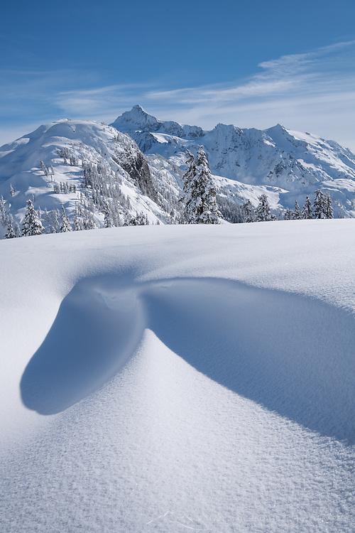 Austin Pass snowdrift, Mount Shuksan is in the distance. Heather Meadows Recreation Area, North Cascades Washington
