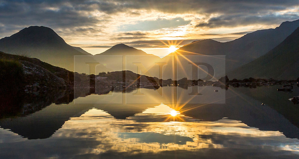 © Licensed to London News Pictures. 07/07/2018. Wasdale Head UK. The sun rises this morning between Great Gable & Scafell Pike mountains at Wast Water in Wasdale, Cumbria, as the UK heatwave is set to continue throughout the weekend. Photo credit: Andrew McCaren/LNP