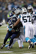 Seattle Seahawks running back Robert Turbin (22) gets tackled by Carolina Panthers linebacker Adarius Glanton (57) as he runs the ball during the NFL week 19 NFC Divisional Playoff football game against the Carolina Panthers on Saturday, Jan. 10, 2015 in Seattle. The Seahawks won the game 31-17. ©Paul Anthony Spinelli