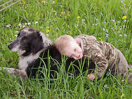 A male toddler lays on the back of his pet border collie dog.